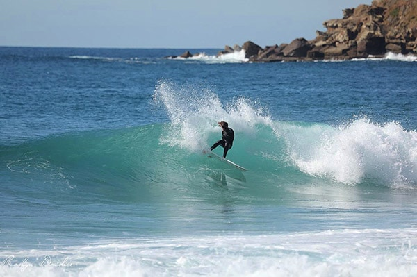 A-male-adult-rides-a-larger-wave-at-Macmasters-Beach