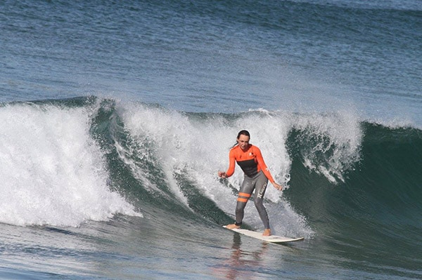 Adult-rides-a-larger-wave-at-Macmasters-Beach