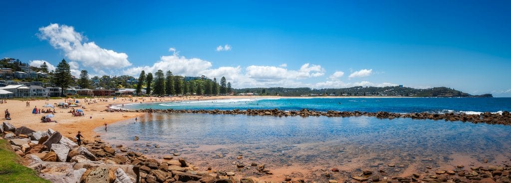 Avoca Beach side on looking toward the blue water and sky with a small crowrd of people on the sandy beach itself