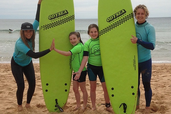 Coaches-high-five-students-with-surf-boards