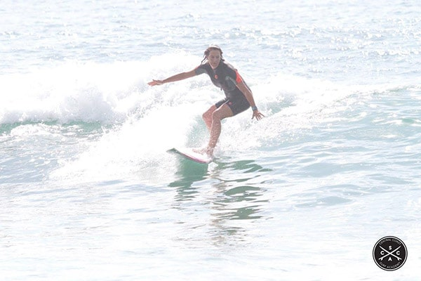 Staff-memeber-surfs-on-wave-with-blue-water