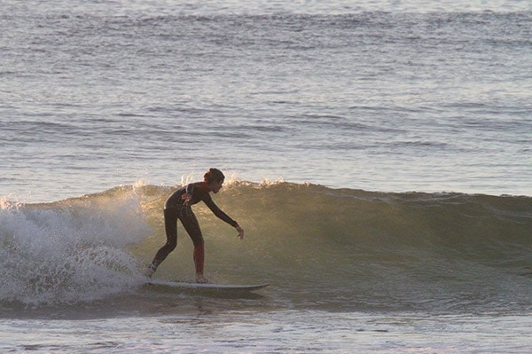 surfer-rides-a-small-wave-with-the-sun-in-the-distance