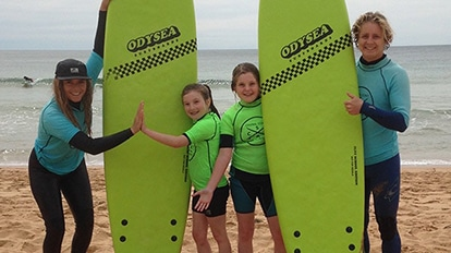 Coaches-high-five-students-with-surf-boards---Mini-Grooms